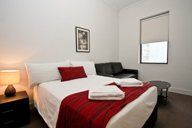 king sized bed in white linen and towel and couch on the side at king sized bed with black duvet cover and a window on the side, star apartments