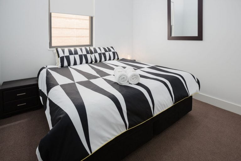 king sized bed in with duvet cover in geometric pattern at star apartments