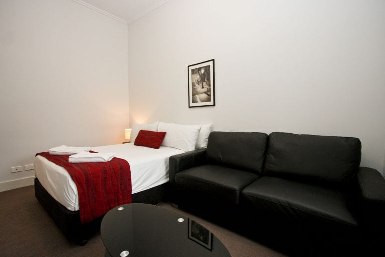 double sized bed in white bedding with some touches of red and a couch on the side